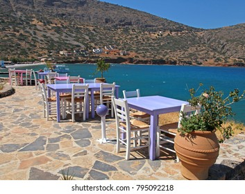 Landscape with traditional greek tavern with pink and lilac tables and white chairs overlooking Mediterranean sea, Crete, Greece.