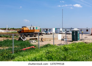 Landscape transform into urban area with machinery, people are working on unfinished modern edifice. View on construction site.