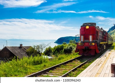 Landscape for travel with the arrival of a red train on a wooden deserted platform railway in a village on Lake Baikal in a bright summer sunny day.