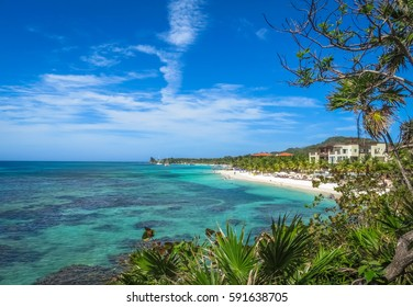 Landscape of a tropical  blue ocean water and sandy beach in Roatan island. Blue cloudy sky in the background.
