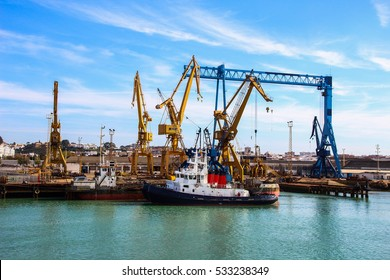 Landscape of tugboats and cranes in shipyard in coast of Huelva, Andalusia, Spain.