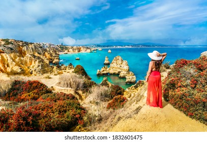 Landscape with unknown tourist girl is looking to the amazing view of spectacular rock formations, with caves, grottoes and sea arches in Lagos, Algarve, Portugal