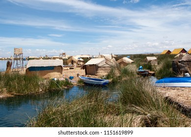 Landscape of the Uros floating islands in the magic blue colors of the Titicaca Lake with the Andes mountain range in the background.
