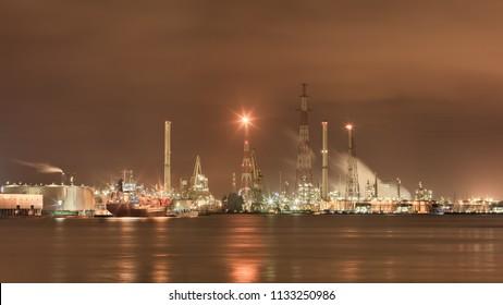 Landscape of the vast harbor area with Illuminated petrochemical production plant, Antwerp, Belgium.