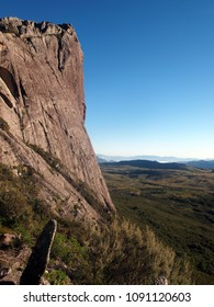 Landscape (vertical) with big tall granite bluff on the left and valley with blue sky on the right. Taken during summit ascent at Andringitra national park, Madagascar.