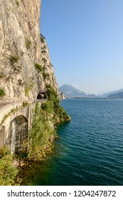 landscape with vertical rock walls flanking road on lakeside, shot in bright fall light near Limone, Brescia, Italy