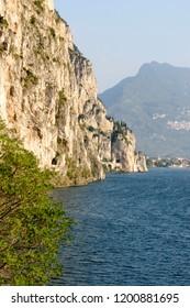 landscape with vertical rock walls on lakeside, shot in bright fall light near Riva del Garda, Trento, Italy