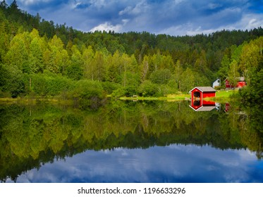 Landscape with vibrant colour in sky, green forest and calm tranquil reflections in water, beauty in nature