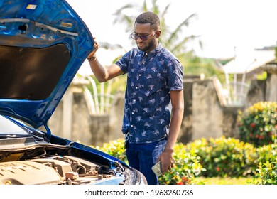 landscape view of african guy standing besides automobile, with opened bonnet- transportation concept