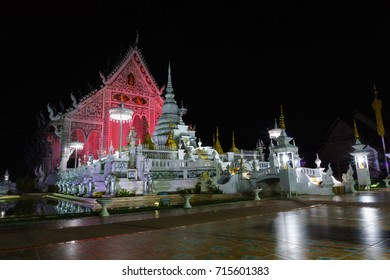 landscape view of ancient burmese style chiang rai temple turning color light on at night. lampang, thailand.