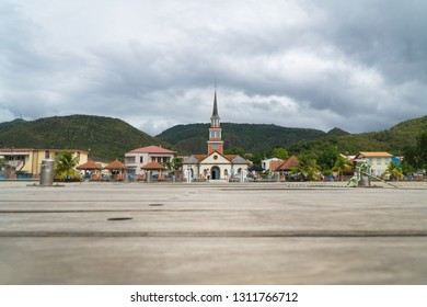Landscape view of Anse d'Arlet village, with its famous church, beach, turquoise water, green forest moutains & clouds in sky, from its wooden landing stage, martinique, dom tom, antilles, West indies