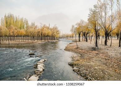 Landscape view of autumn foliage with flowing Hargisa river and cloudy mountain behind the morning fog. Skardu, Gilgit Baltistan, Pakistan.