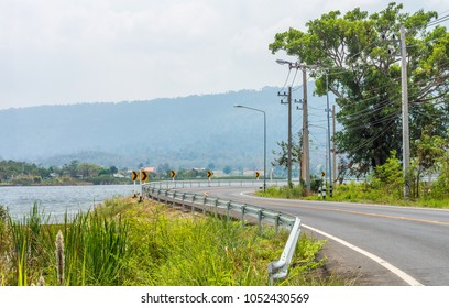 Landscape view at Ban San Kamphaeng reservoir and winding curvy road. They are in Wang Nam Khiao District, Nakhon Ratchasima Province, Thailand, Southeast Asia.