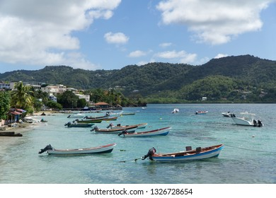 Landscape view of the beautiful village of Sainte Luce, its beach and yole fishermen small boats in the turquoise transparent sea, with green hills and blue sky in background, Martinique, West Indies.