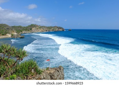 Landscape View of a Blue Ocean at Pantai Drini Beach with Waving Indonesian Flag