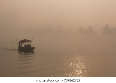 A landscape view of the brahmaputra river national park of the Sundarbans  mangrove forest in a misty or foggy day with a small boat navigating on it, bangladesh