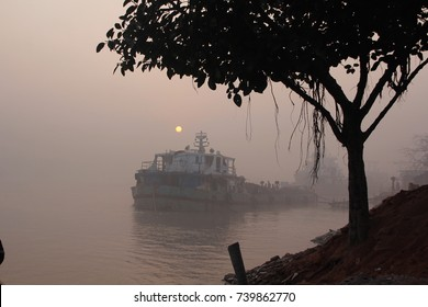 A landscape view of the brahmaputra river national park of the Sundarbans  mangrove forest, in a foggy day with a tree and a rusty old cargo ship, bangladesh
