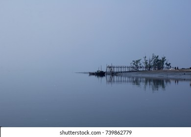 A landscape view of the brahmaputra river national park of the Sundarbans  mangrove forest in a misty or foggy day, with the sky melting on the water bangladesh