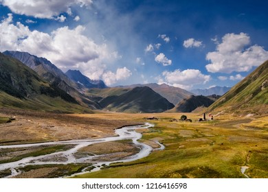 Landscape view of Caucasus mountains, river and stone houses and tower, Kazbegi region, Country of Georgia