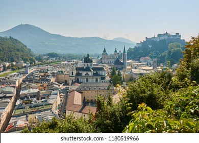 Landscape view of the city of Salzburg in Austria with a cathedral and a castle in the background.