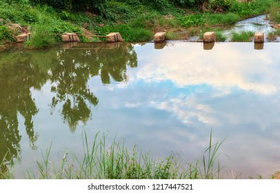 Landscape view of cloud blue sky reflect on water with concrete weir at rural village in Thailand