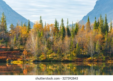 Landscape view of colorful autumn taiga forest with birch, spruce and mountain ash trees reflected in lake in Kunijok valley of Hibiny mountains above the Arctic Circle, Russia