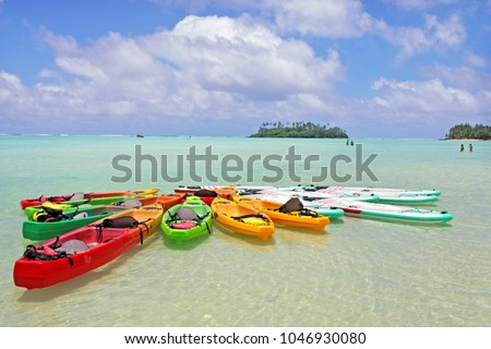 Landscape view of colourful kayaks and  stand up paddle boarding at Muri Lagoon in Rarotonga, Cook Islands.