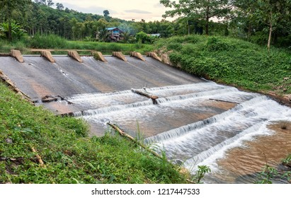 Landscape view of concrete weir with water flowing down at rural village in Thailand