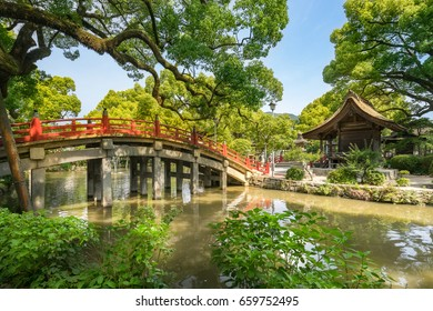 A landscape view from the Dazaifu temple garden, a red bridge over small lake leading to the temple, many big old trees in the garden, a small old wooden shrine at the entrance of the temple. Fukuoka.