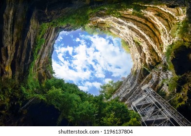 Landscape view of deep natural rock cave with shaft and sky background