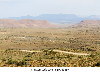 Landscape view of dirt roads weaving through the mountains and plains of Karoo National Park in South Africa
