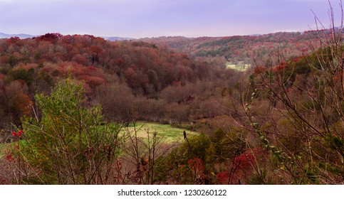 Landscape view during fall in Blue Ridge Georgia, USA surrounded by colorful leaves and a small red house hidden in the valley
