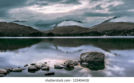 Landscape View from the edge of a Lake with rocks in the foreground