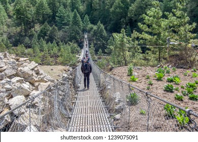 Landscape view of entrance to suspension bridge. One alpinist is passing over the bridge.Sagarmatha (Everest) National Park, Nepal.