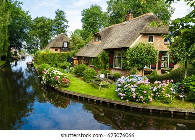 Landscape view of famous Giethoorn village with canals and rustic thatched roof houses in farm area.