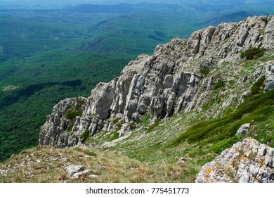 Landscape view fro the rocky mountains. The valley is covered with forest. Nice place for travel and hiking. Rocky slopes on the top. Untouched nature.