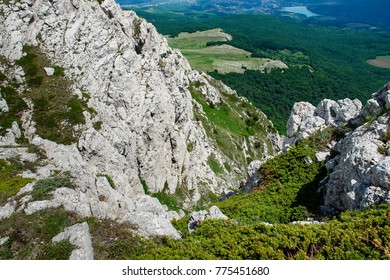 Landscape view fro the top of a mountain. With a valley and small town down. Forests in valley. The rock is covered with moss and bushes.