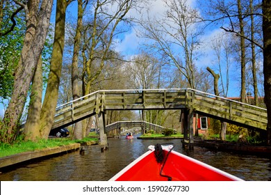 landscape and view of Giethoorn village in Netherlands (Holland) near Amsterdam, canal boat trip and old typical and traditional vintage thatched houses (cottage), famous attraction, destination.