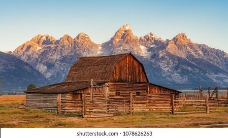 Landscape view of Grand Teton mountain range and abandoned barn, Wyoming, USA