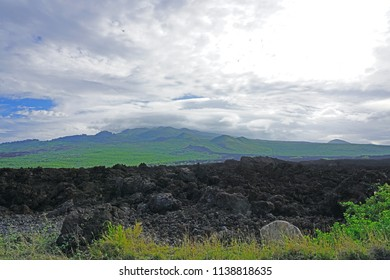 Landscape view of green fields on the slopes of the Haleakala volcano and black lava rocks at Makena park, Maui, Hawaii