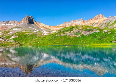 Landscape view of green meadow and Ice lake water reflection near Silverton, Colorado in August 2019 summer on summit with snow and peak