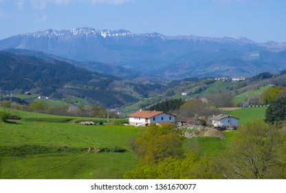 landscape view of green meadows mountains and a small farm, Basque Country, Spain