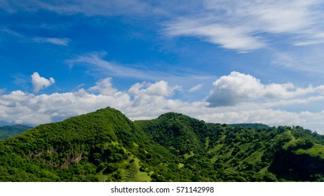 Landscape view of green mountains and blue sky with clouds at Candidasa Beach, Bali, Indonesia. Aerial view.