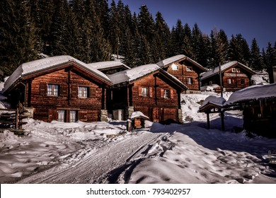 Landscape View Of A Group Traditional Swiss Chalets With Roofs Covered By Snow And