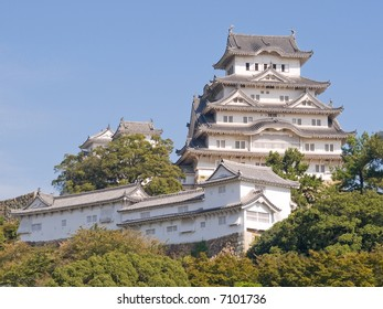 Landscape view of Himeji Castle on the hillside during the daytime with trees in the foreground and a clear blue sky in the background