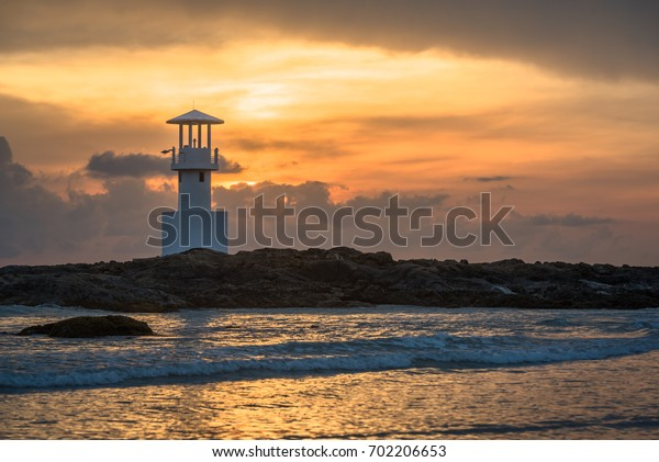 Landscape view of light beacon or lighthouse on the rock coast at sunset sky in twilight.