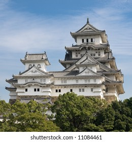 Landscape view of the main tower of Himeji Castle on the hillside during the daytime with trees of the castle grounds in the foreground and blue sky with thin white clouds in the background