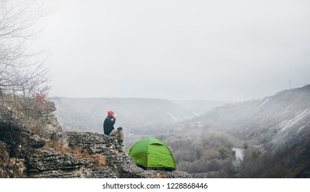 Landscape view of a man traveler relaxing in mountains near of tent camping gear outdoor. Male relaxing after hiking in the mountain. Travel, lifestyle, sport and hiking active vacation concept.