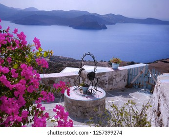 Landscape View of Milos Island with Bougainvilleas and Water Well