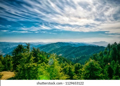 landscape view of the mountain with fluffy cloudy sky and green trees or forest